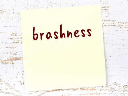 Concept of reminder about brashness. Yellow sticky sheet of paper on wooden wall with inscription