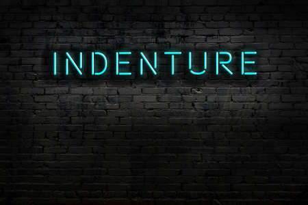 Neon sign with inscription indenture against brick wall. Night view
