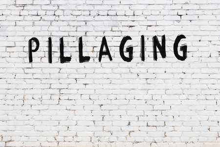 White brick wall with inscription pillaging handwritten with black paint