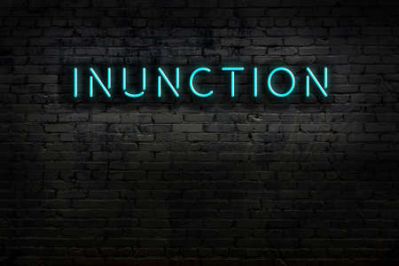 Neon sign on brick wall at night. Inscription inunction