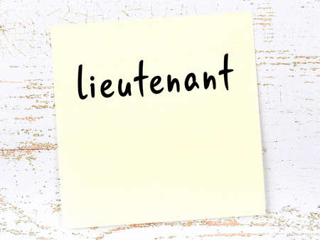 Concept of reminder about lieutenant. Yellow sticky sheet of paper on wooden wall with inscription
