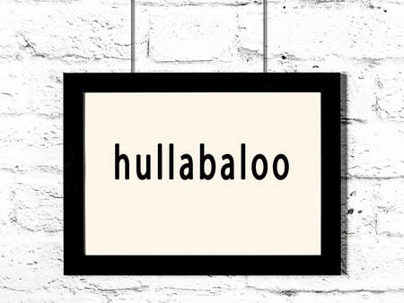 Black wooden frame with inscription hullabaloo hanging on white brick wall