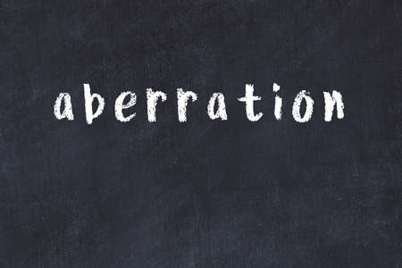 Chalk handwritten inscription aberration on black desk