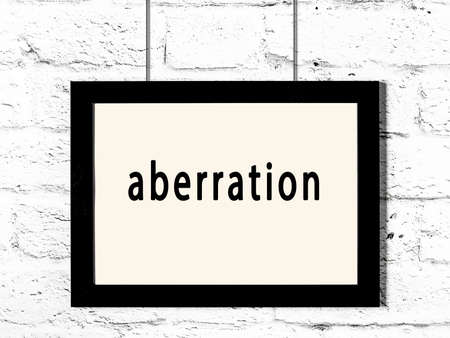 Black wooden frame with inscription aberration hanging on white brick wall