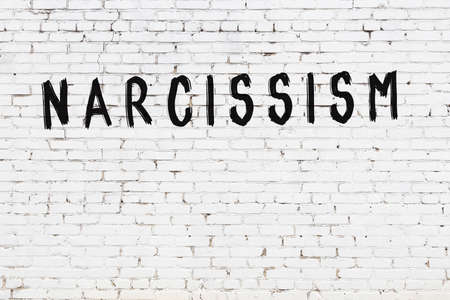 White brick wall with inscription narcissism handwritten with black paint