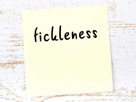 Concept of reminder about fickleness. Yellow sticky sheet of paper on wooden wall with inscription