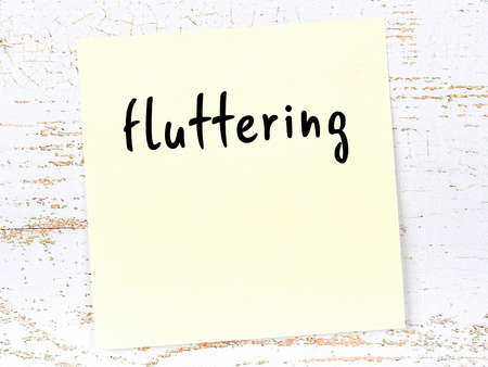 Concept of reminder about fluttering. Yellow sticky sheet of paper on wooden wall with inscription