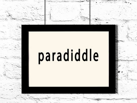 Black wooden frame with inscription paradiddle hanging on white brick wall