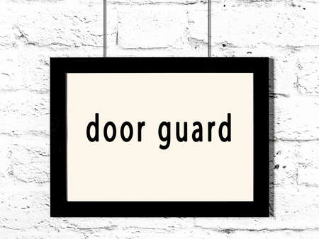 Black wooden frame with inscription door guard hanging on white brick wall