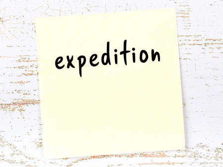 Concept of reminder about expedition. Yellow sticky sheet of paper on wooden wall with inscription