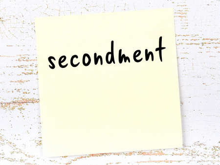 Concept of reminder about secondment. Yellow sticky sheet of paper on wooden wall with inscription