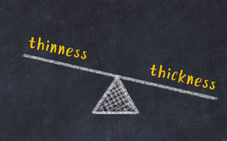Chalk drawing of scales with words thinness and thickness on black board. Concept of balance