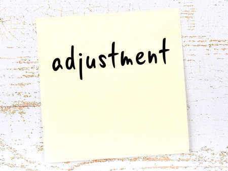 Concept of reminder about adjustment. Yellow sticky sheet of paper on wooden wall with inscription