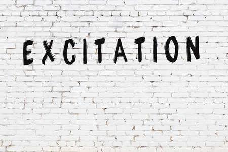 Inscription excitation written with black paint on white brick wall. 版權商用圖片