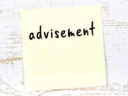 Concept of reminder about advisement. Yellow sticky sheet of paper on wooden wall with inscription