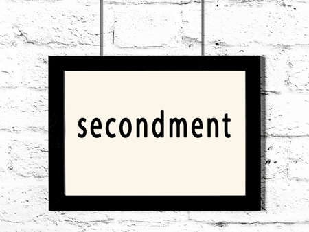 Black wooden frame with inscription secondment hanging on white brick wall