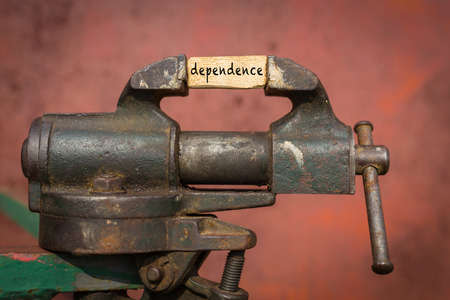 Concept of dealing with problem. Vice grip tool squeezing a plank with the word dependence