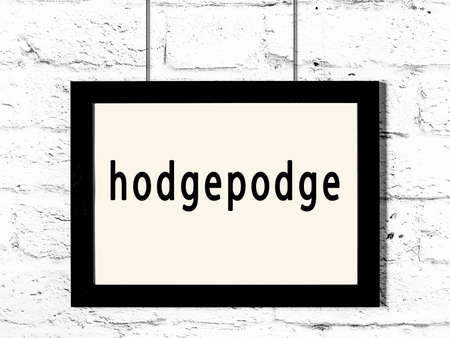 Black wooden frame with inscription hodgepodge hanging on white brick wall