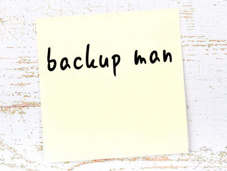 Concept of reminder about backup man. Yellow sticky sheet of paper on wooden wall with inscription
