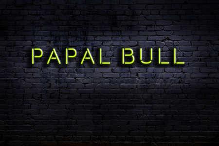 Neon sign on brick wall at night. Inscription papal bull
