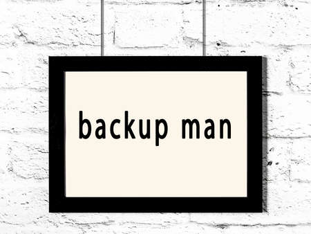 Black wooden frame with inscription backup man hanging on white brick wall