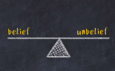 Chalk drawing of scales with words belief and unbelief on black board. Concept of balance