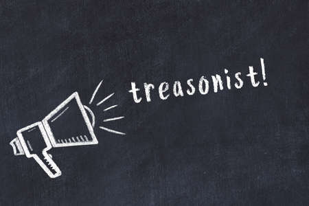 Chalk drawing of loudspeaker and handwritten inscription treasonist on black desk