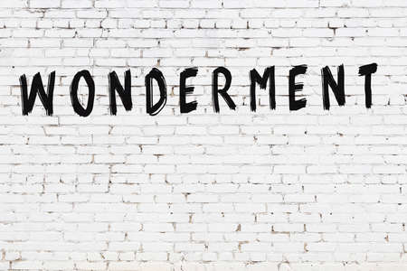 Inscription wonderment written with black paint on white brick wall.