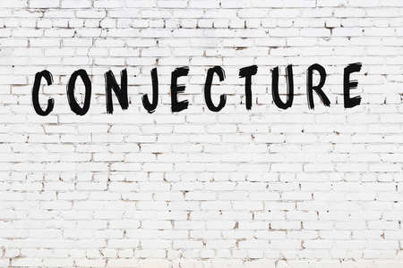 White brick wall with inscription conjecture handwritten with black paint