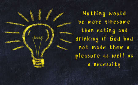 Wise quotation and a chalk drawing of a bulb on black chalkboard Standard-Bild