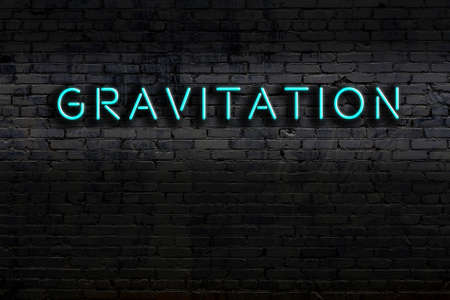 Neon sign with inscription gravitation against brick wall. Night view