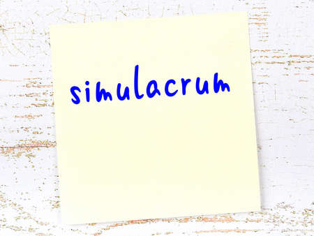 Concept of reminder about simulacrum. Yellow sticky sheet of paper on wooden wall with inscription