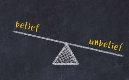 Concept of balance between belief and unbelief. Black chalboard with sketch of scales and words on it