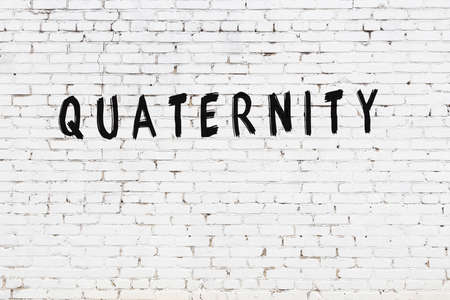 White brick wall with inscription quaternity handwritten with black paint
