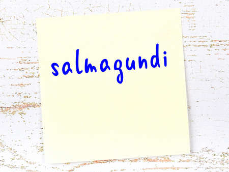 Concept of reminder about salmagundi. Yellow sticky sheet of paper on wooden wall with inscription