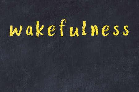 Chalk handwritten inscription wakefulness on black desk