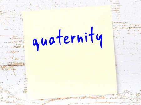 Concept of reminder about quaternity. Yellow sticky sheet of paper on wooden wall with inscription