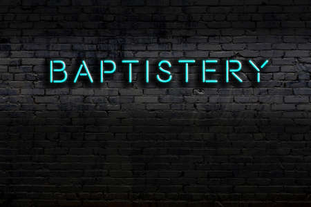 Neon sign on brick wall at night. Inscription baptistery