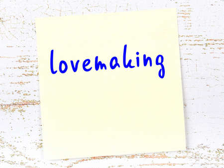 Yellow sticky note on wooden wall with handwritten inscription lovemaking