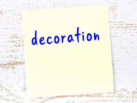Concept of reminder about decoration. Yellow sticky sheet of paper on wooden wall with inscription