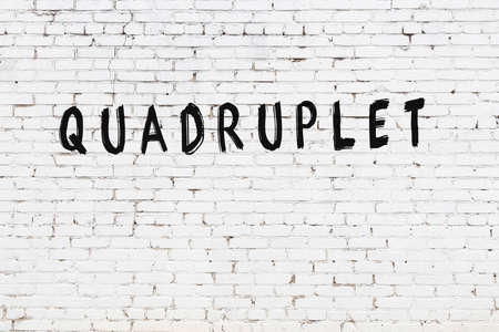 White brick wall with inscription quadruplet handwritten with black paint