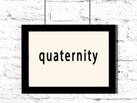 Black wooden frame with inscription quaternity hanging on white brick wall
