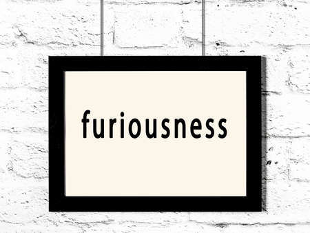 Black wooden frame with inscription furiousness hanging on white brick wall