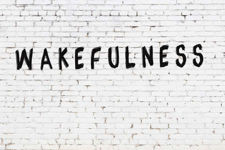 White brick wall with inscription wakefulness handwritten with black paint