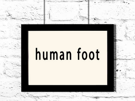 Black wooden frame with inscription human foot hanging on white brick wall
