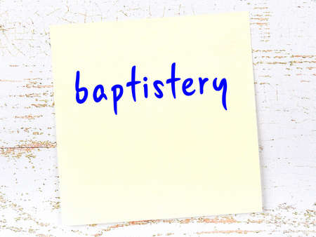 Concept of reminder about baptistery. Yellow sticky sheet of paper on wooden wall with inscription