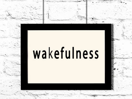 Black wooden frame with inscription wakefulness hanging on white brick wall