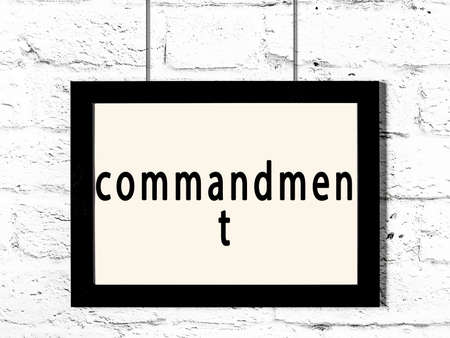 Black wooden frame with inscription commandment hanging on white brick wall