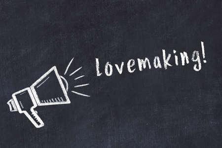 Chalk drawing of loudspeaker and handwritten inscription lovemaking on black desk