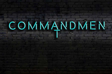 Neon sign with inscription commandment against brick wall. Night view
